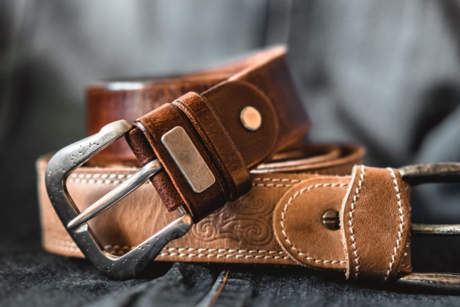 Two brown leather belts on dark background. Front view